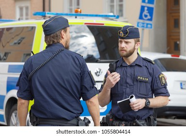 STOCKHOLM, SWEDEN - JUNE 08, 2017: Two Swedish male police officers discussing in front of a police car in Stockholm, Sweden, June 08, 2017