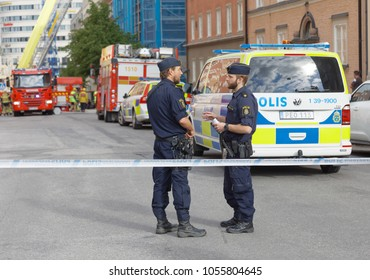 STOCKHOLM, SWEDEN - JUNE 08, 2017: Swedish police officers working in front of fire trucks and police cars in Stockholm, Sweden, June 08, 2017