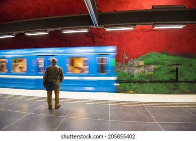 STOCKHOLM, SWEDEN - JUNE 10, 2014: Train arrives Solna Centrum metro station on June 10, 2014 in Stockholm, Sweden. This station was painted in 1975 by artists Anders Aberg and Karl-Olov Bjork.