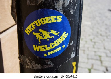 "STOCKHOLM, SWEDEN -?? JUNE 14, 2017: A ""Refugees Welcome"" sticker is stuck to a pole in one of the main streets in Stockholm in the summer"