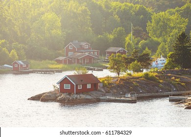 STOCKHOLM, SWEDEN - JUNE 19, 2016: Small picturesque coastal village of Moja in the swedish archipelago with red houses. Summerhaze