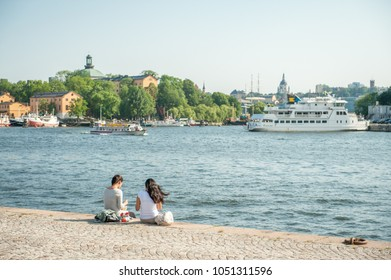 STOCKHOLM, SWEDEN - JUNE 22, 2011: Female tourists enjoy a picnic at Nybroviken waterfront in Stockholm. The city is built on 17 islands and can be enjoyed by cruising some of the local ferries.