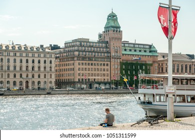 STOCKHOLM, SWEDEN - JUNE 22, 2011: Young man enjoys a picnic at Nybroviken waterfront in Stockholm. The city is built on 17 islands and can be enjoyed by cruising some of the local ferries.