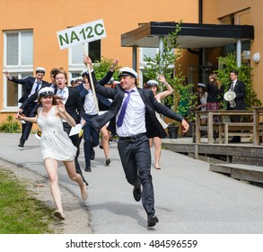 Stockholm, Sweden - June 5, 2015: Group of happy teenagers wearing graduation caps running out from school after graduation from high school at the school, Tullinge Gymnasium