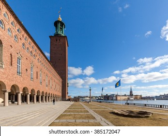 Stockholm, Sweden - Mar 1, 2016 : View of Stockholm City hall and its waterfront yard. Stockholm county flag and Riddarholmen island are shown in the right center.