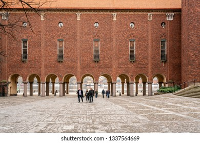 STOCKHOLM, SWEDEN - MARCH 15, 2016: Exterior front view of a small group of people in front of Stadshuset, City Hall. Red brick building with arches and windows in Stockholm Sweden March 15, 2016.