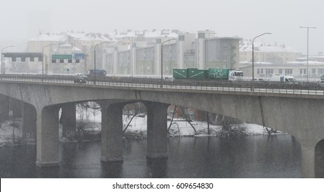 Stockholm, Sweden - Mars 7, 2017: Cars driving on a snowy day at Essingeleden, a motorway in central Stockholm, in the background there is Lilla Essingen, an island and a district in central Stockholm