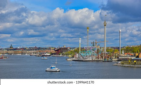 STOCKHOLM, SWEDEN - May 03, 2019: A SL DJURGARDEN 8 ferry, public transport of the city of Stockholm, passes underway in front of Grona Lund amusement park and a tourboats in Stockholm harbour.