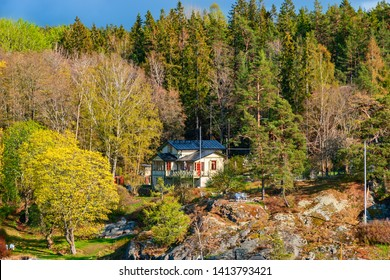 STOCKHOLM, SWEDEN - May 03, 2019: Picturesque spring coastal landscape of Stockholm archipelago with waterfront mansion surrounded by bare trees and the coniferous forest.