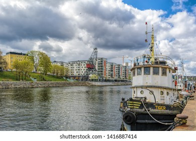 STOCKHOLM, SWEDEN - May 03, 2019: Vintage boats moored at Hammarby canal embankment in front of waterfront apartment buildings at sunny spring day.