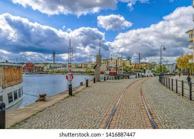 STOCKHOLM, SWEDEN - May 03, 2019: Hammarby canal embankments with moored vintage boats, cobblestoned promenade and waterfront apartment buildings at sunny spring day.