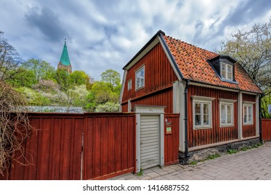 STOCKHOLM, SWEDEN - May 03, 2019: A typical swedish residential house painted in traditional falun red with wooden fence against the Sofia Church in the background in Vitabergsparken, Sodermalm.