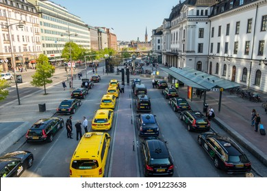 STOCKHOLM, SWEDEN - MAY 11, 2018: Horizontal high wide angle city view of many yellow and black taxis in line in the city of Stockholm May 11, 2018. Taxi drivers talking in the foreground.