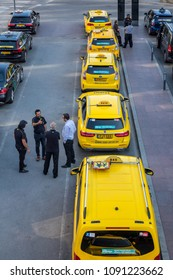 STOCKHOLM, SWEDEN - MAY 11, 2018: Vertical high angle city view of many yellow and black taxis in line in the city of Stockholm May 11, 2018. Taxi drivers talking in the foreground.
