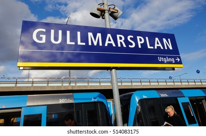 Stockholm, Sweden - May 13, 2014:: Gullmarsplan metro station with the station sign, speaker, subway trains and passengers.