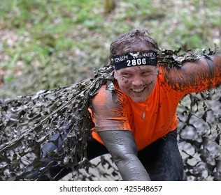 STOCKHOLM, SWEDEN - MAY 14, 2016: Smiling man covered with mud crawling under a camouflage net in the obstacle race Tough Viking Event in Sweden, April 14, 2016