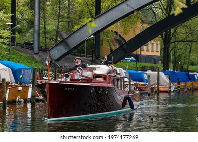 Stockholm, Sweden May 15, 2021 A man maneuvers a classic wooden boat in the Palsundet canal on Sodermalm.