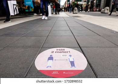 Stockholm, Sweden May 16, 2020 Signs on Drottninggatan, a busy shopping street, tell people in Swedish to stay two meters apart from each other.