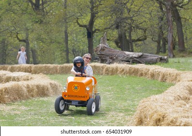 STOCKHOLM, SWEDEN - MAY 21, 2017: Smiling boy and mother driving a orange soapbox car downhill on a field in the race Gardesloppet at Djurgarden, Stockholm, Sweden. May 21, 2017