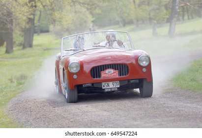 STOCKHOLM, SWEDEN - MAY 22, 2017: Red Allard Oetta classic car from 1953 driving on a country road in the public race Gardesloppet in the forests at Djurgarden, Stockholm, Sweden. May 22, 2017