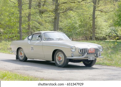 STOCKHOLM, SWEDEN - MAY 22, 2017: White Volvo P1800 S classic car from 1963 driving on a country road in the public race Gardesloppet in the forests at Djurgarden, Stockholm, Sweden. May 22, 2017