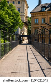 STOCKHOLM, SWEDEN - MAY 26, 2018: Perspective view of a pedestrian passage with steel fence  between buildings in Stockholm May 26, 2018. Incidental people in the background.