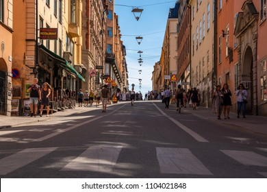 STOCKHOLM, SWEDEN - MAY 26, 2018: Low angle view of people walking on a city shopping street in Stockholm Sweden May 26, 2018.