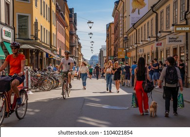 STOCKHOLM, SWEDEN - MAY 26, 2018: Front view of cyclists at a pedestrian city shopping street in Stockholm May 26, 2018. Incidental people walking by in the foreground and background.