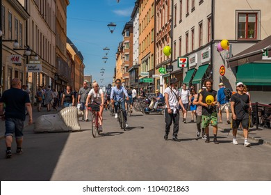 STOCKHOLM, SWEDEN - MAY 26, 2018: Front view of a couple cycling at a pedestrian city shopping street in Stockholm May 26, 2018. Incidental people walking by in the foreground and background.