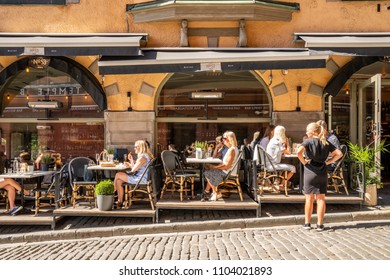 STOCKHOLM, SWEDEN - MAY 26, 2018:  Profile view of a outdoor restaurant with many guests having dinner and a female waitress in the foreground in Stockholm May 26, 2018.