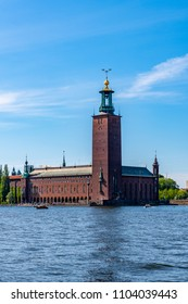 STOCKHOLM, SWEDEN - MAY 26, 2018: Beautiful summer front view of the famous brick building City Hall by the water in Stockholm Sweden May 26, 2018.