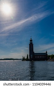 STOCKHOLM, SWEDEN - MAY 26, 2018: Beautiful backlit summer front view of the famous brick building City Hall by the water in Stockholm Sweden May 26, 2018.