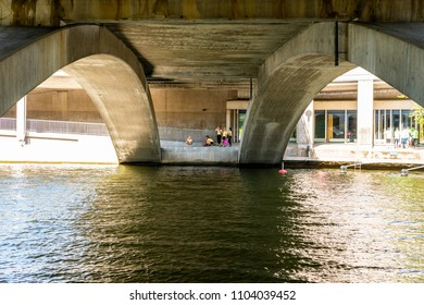 STOCKHOLM, SWEDEN - MAY 26, 2018:  Perspective view under a concrete bridge by the water in Stockholm May 26, 2018. Groups of people in the background.