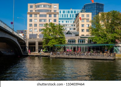 STOCKHOLM, SWEDEN - MAY 26, 2018:  Profile view of a outdoor restaurant in the city by the water with many guests having dinner in Stockholm May 26, 2018.