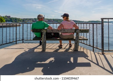 STOCKHOLM, SWEDEN - MAY 26, 2018: Back view of a senior couple sitting on a bench in the sun overlooking the water in Stockholm Sewden May 26, 2018.