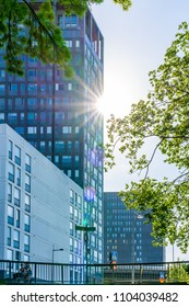 STOCKHOLM, SWEDEN - MAY 26, 2018: Low angle view of modern office building with trees and sun light flare in Stockholm May 26, 2018. Incidental people in the foreground.