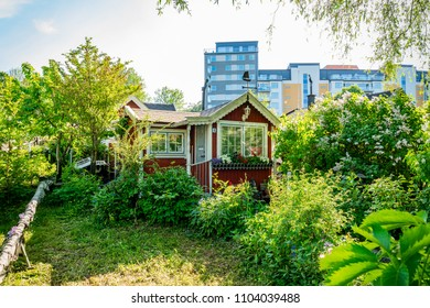 STOCKHOLM, SWEDEN - MAY 26, 2018: Front view of  a small traditional wooden cottage in the city with mordern office buildings in the background in Stockholm May 26, 2018.