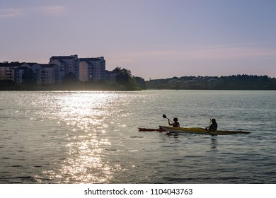 STOCKHOLM, SWEDEN - MAY 26, 2018: Backlit sunset view of a couple canoeing in the city with buildings in the background in Stockholm May 26, 2018.