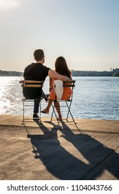 STOCKHOLM, SWEDEN - MAY 26, 2018: Back view of a young couple sitting on chairs at a quay by the water looking at the sunset in Stockholm May 26, 2018.