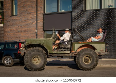 STOCKHOLM, SWEDEN - MAY 26, 2018: Profile view of people in an open offroad car with giant tires parking in the city of Stockholm May 26, 2018.