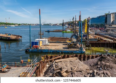 STOCKHOLM, SWEDEN - MAY 26, 2018: Landscape view of a large construction site with cranes at the water's edge with people working. The reconstruction of Slussen Stockholm Sweden May 26, 2018.