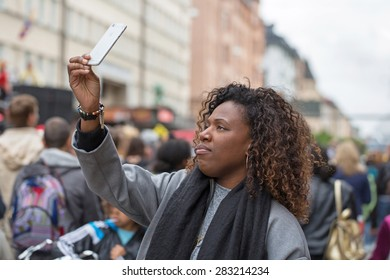 STOCKHOLM, SWEDEN - MAY 31, 2015. Peace and Love Parade. Street party in Stockholm, Female takes selfie.