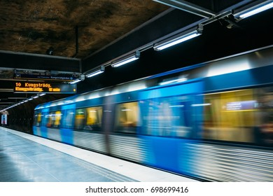 Stockholm, Sweden. Modern Illuminated Metro Underground Subway Station In Blue And Gray Colors With Moving Train.