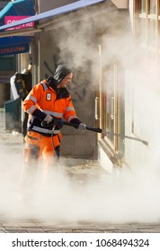 STOCKHOLM, SWEDEN - NOV 07, 2017: Official in orange uniform working to remove graffiti using steem on a wall in central Stockholm, Sweden, November 07, 2017