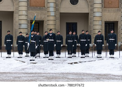"Stockholm, Sweden - November 22 2017 - Air Force troop performs changing of the guards in front of the Royal Palace ""Kungliga Slosset"" on a snowy and cold day caring their colors and the Swedish flag."
