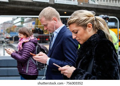 STOCKHOLM, SWEDEN - NOVEMBER 5, 2015: People busy watching their phones in Stockholm city centre, Sweden