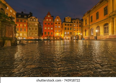 STOCKHOLM, SWEDEN - OCT 28, 2017: Stortorget in Stockholm during autumn evening with a couple standing still during the long exposure. Low angle view with wet cobblestones in focus