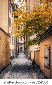STOCKHOLM, SWEDEN - October 14, 2016: View from narrow and idyllic street with colorful buildings in Gamla Stan. The Old Town in Stockholm, Sweden. Cloudy day.