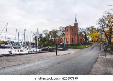 Stockholm, Sweden - October, 24th, 2016. Skridskopaviljongen, small brick church and parked yachts in harbor of Kastellholmen island, in Norrmalm, Stockholm, Sweden. View from Kastellholmsbron bridge.