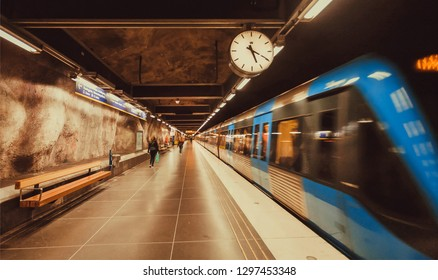 STOCKHOLM, SWEDEN - SEP 17: Motion blur from metro train driving past underground station with clock on September 17, 2018. Stockholm metro system has 100 stations with arts, mosaics